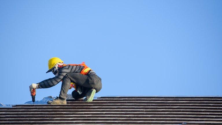 a professional roofer doing regular roof maintenance work
